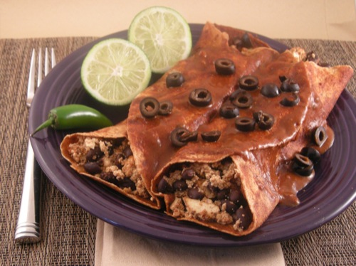 vegan smokey black bean burritos covered in sauce and topped with black olives