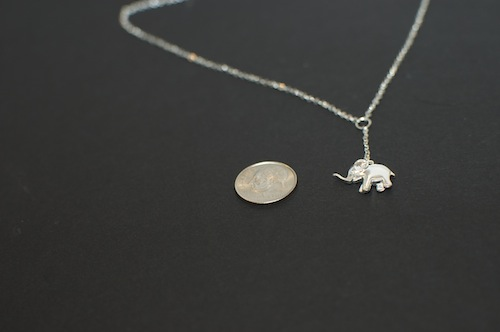 comparison of the elephant charm to the size of a dime