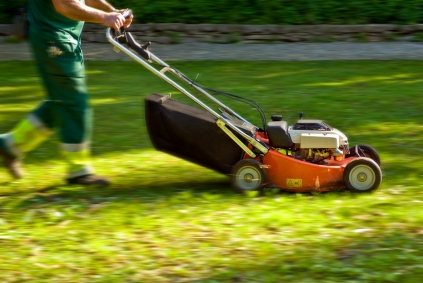 bottom half of person pushing lawn mower