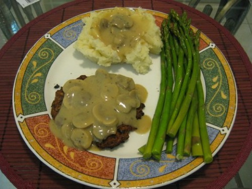 mushroom gravy over mushroom burger and mashed potatoes with a side of asparagus