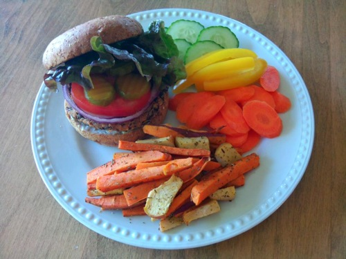 Black bean burger with red onion, tomato, pickles, and lettuce on a bun with a side of sweet potato and yellow squash fries, and raw slices of carrots, cucumbers, and yellow bell pepper
