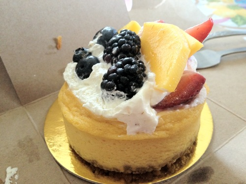 small vegan mango cheesecake topped with mango slices and blackberries