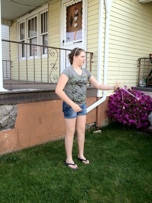 girl standing in front yard twirling baton